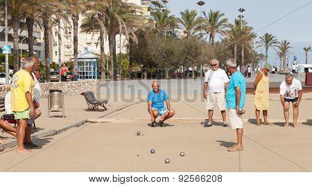Seniors Spaniards Play Bocce On Sandy Beach