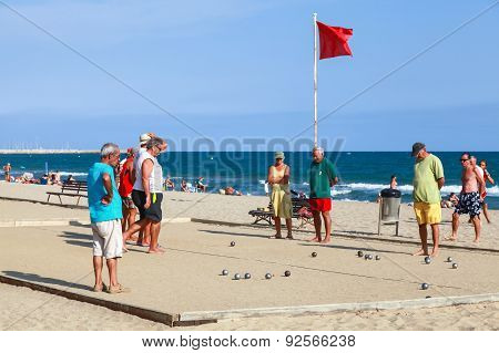 Seniors Men Play Bocce On Sandy Beach In Spain