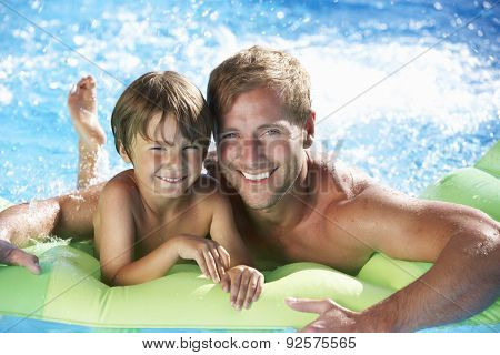 Father And Son On Holiday In Swimming Pool