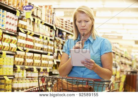 Woman In Grocery Aisle Of Supermarket With List poster
