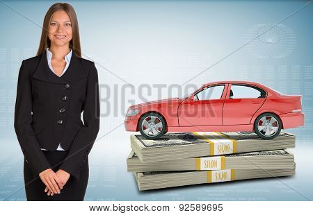 Businesslady with car standing on bundle of money