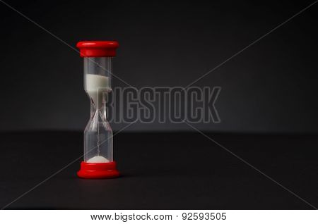 red hourglass in front of a black background