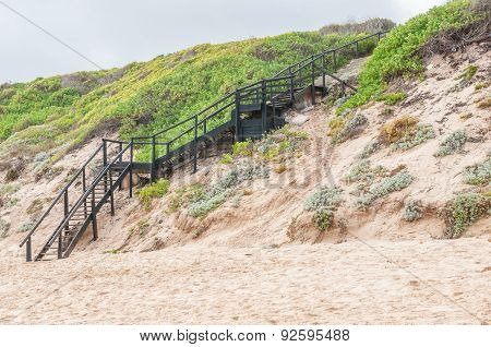 A staircase from the top of the dune down to the beach in Reebok near Mosselbay South Africa poster