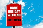 Bank Holiday Weekend Just Ahead motivational quote written on red road sign isolated over clear blue sky background. Concept image with available copy space poster