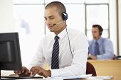 Friendly Service Agent Talking To Customer In Call Centre poster