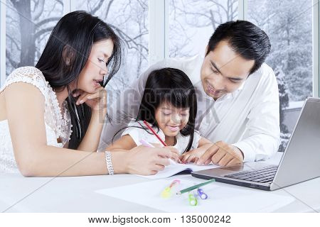 Happy family and their daughter doing schoolwork while using laptop and write on the book at home