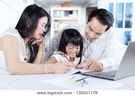 Photo of a cheerful little girl and her parents doing schoolwork while writing on the book and using laptop at home