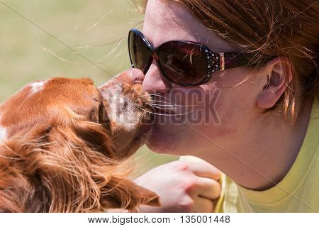 SNELLVILLE, GA - MAY 14 2016:  A young woman and her dog compete in a kissing contest at Pawfest a dog festival on May 14 2016 in Snellville GA.