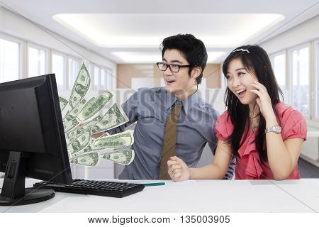 Portrait of two happy workers earn money online and look at the money on the monitor