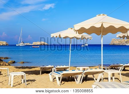 Beach chair and colorful umbrella on the beach in sunny