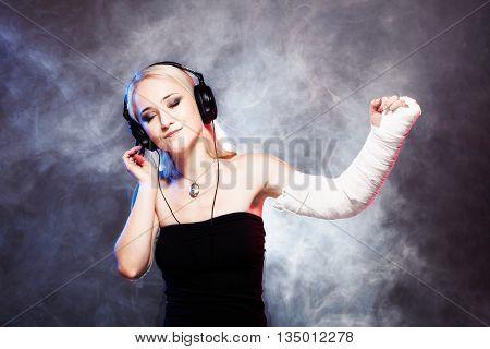 Girl Dancing With Broken Arm And Headphones