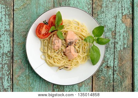 Portion of spaghetti with basil tomatoes and salmon on old turquoise table overhead view