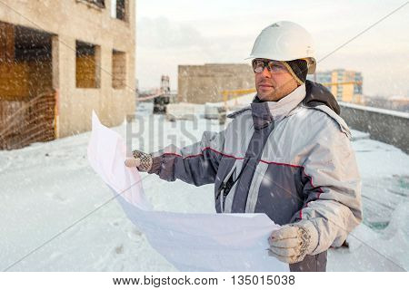Civil Engineer at construction site is inspecting ongoing production according to design drawings in winter.