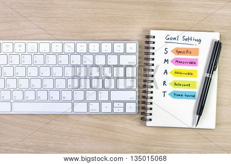 smart goals setting written on the notebook with pen and keyboard over wooden table business success concept