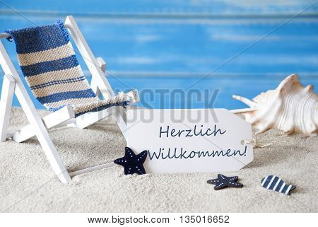Summer Label With German Text Herzlich Willkommen Means Welcome. Blue Wooden Background. Card With Holiday Greetings. Beach Vacation Symbolized By Sand, Deck Chair And Shell.