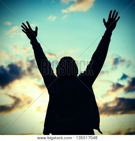 Vignetting Photo of Happy Man Silhouette with Hands Up on the Sunset Background