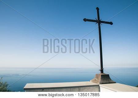 Beautiful blue sky with striking cross above ocean