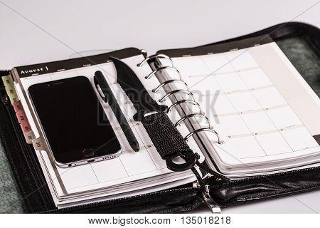 plan for murderer - calendar planner cellphone pen and knife as weapon