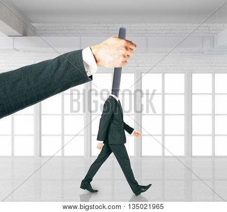 Hand manipulating lever-headed businessman in white brick interior. Concept of control