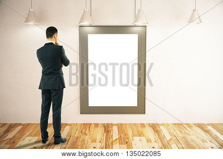 Thoughtful businessman looking at blank picture frame in room with concrete wall wooden floor and ceiling lamps. Mock up 3D Rendering