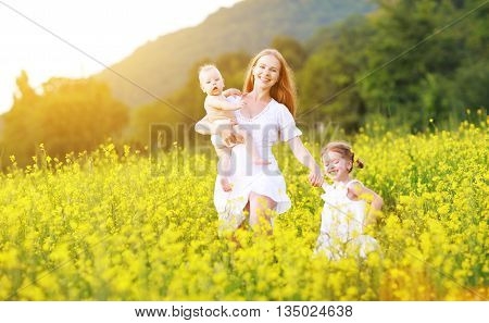 happy family mother and children girl little daughter and baby running on meadow with yellow flowers