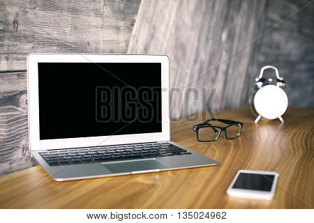 Side view of laptop with blank screen on wooden desktop with smart phone alarm clock and glasses. Mock up