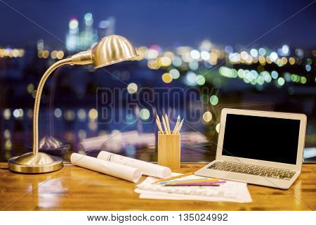 Front view of wooden desktop with blank laptop table lamp paperwork and stationery items on blurry night city background. Mock up
