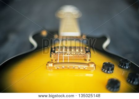 Blurry black and yellow electric guitar. Closeup