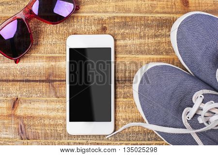 Top view of smart phone with blank screen stylish glasses and blue sneakers on wooden surface. Mock up