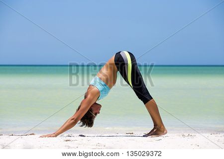Woman practicing yoga at the beach, in a sunny day in the mexican Caribbean