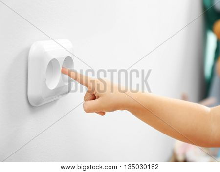 Little child putting finger in power socket, closeup