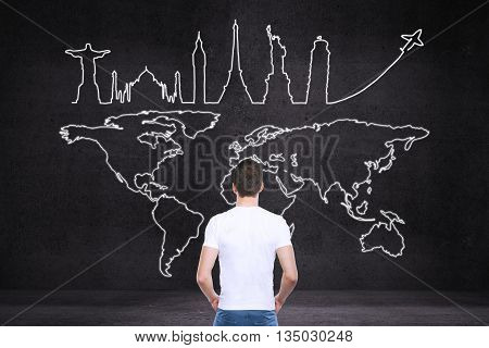 Back view of young man looking at map and sights sketch on dark concrete background. Travel concept