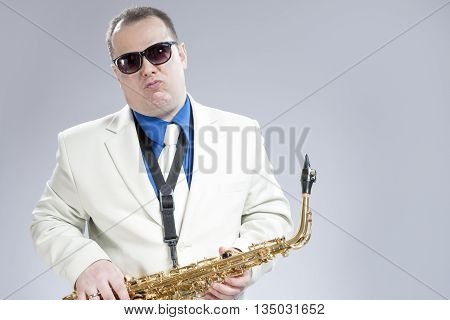 Expressive Funny Male Saxo Player in White Suit Posing with Saxophone Against White Background. Horizontal Image Composition
