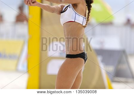Volleyball player is a fit strong female athelete recieving serve in a beach volleyball match.
