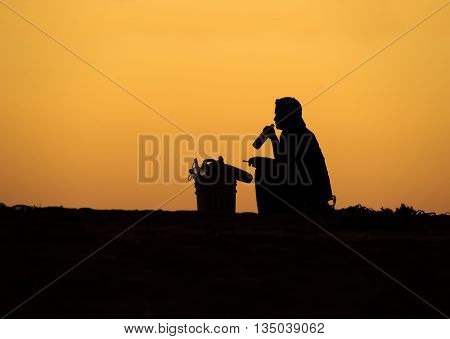 A man is is sitting drinking a beer and smoking a cigarette silhouetted against a bright orange sunset sky.