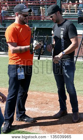 ARLINGTON, TX - APR 18: Recording artist Luke Bryan (R) and his tour manager Mark Sizemore at the ACM & Cabela's Great Outdoor Archery Event at the Texas Rangers Youth on April 18, 2015.