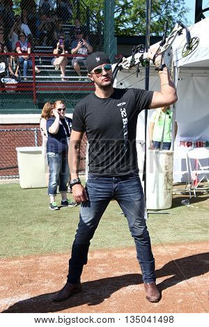 ARLINGTON, TX - APR 18: Recording artist Luke Bryan poses with a bow at the ACM & Cabela's Great Outdoor Archery Event at the Texas Rangers Youth Ballpark on April 18, 2015.
