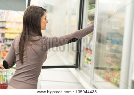 Woman taking deep frozen food from a freezer in a supermarket