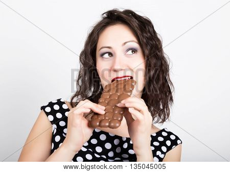 Beautiful young woman eating a chocolate bar, wears a dress with polka dots.