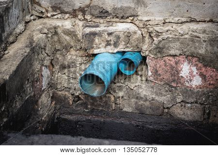 Blue PVC water pipe in dirty underground sewer for dredging drain tunnel cleaning selective focus