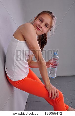 Indoor portrait of young sportive teen girl with a bottle of drinking water while relaxing a in gym leaning against the wall