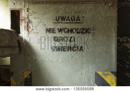 Danger of the loss of life sign on the door of disused nuclear weapons store bunker Soviet cold-war time military base disused. Brzeznica Zachodniopomorskie province Poland
