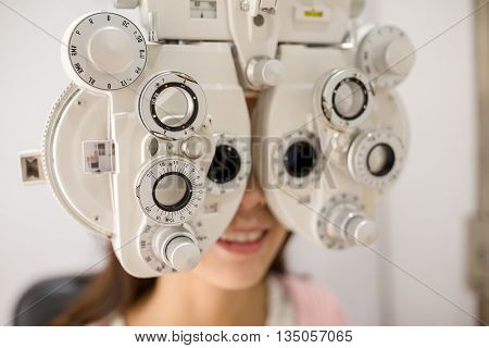 Female patient looking through phoropter during eye exam