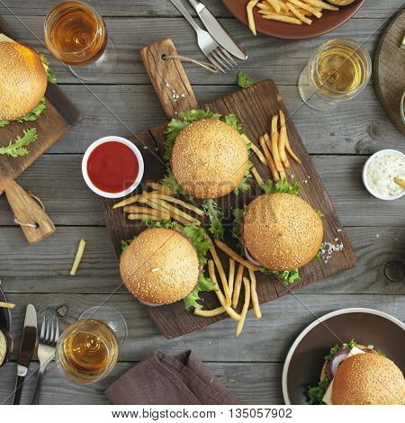 Different burgers and wine on the wooden table top view. Outdoors food Concept