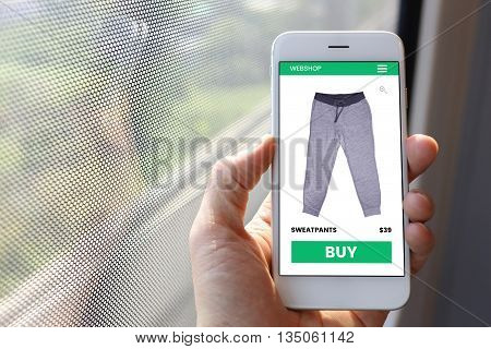 Hand holding smartphone with sweatpants ecommerce screen website