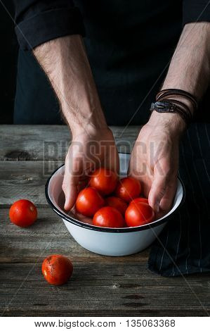 Tomatoes in hands of male chef. Man washing small heirloom tomatoes in bowl on rustic wooden table. Summer harvest, clean healthy lifestyle and cooking concept
