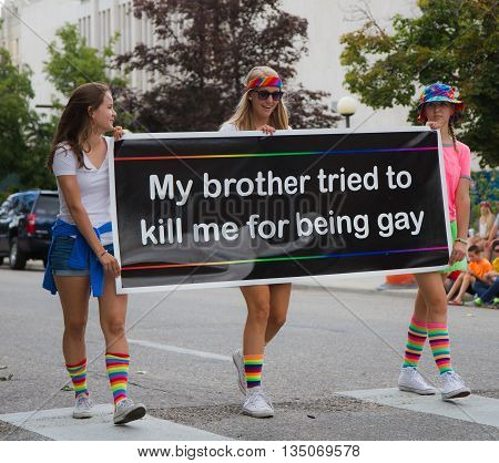 BOISE IDAHO/USA - JUNE 20 2016: Teens walking with a sign regarding a refugee during Boise pridefestival