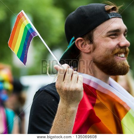 BOISE IDAHO/USA - JUNE 20 2016: Man walking around with a gay pride flag during Boise Pridefest