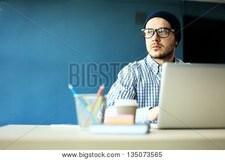 Photo young and talented finance manager working with new project. Handsome man working from his home office. Analyze business plans on laptop. Blurred background, film effect