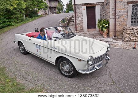 TEODORANO FC ITALY - JUNE 12: driver and co-driver on a vintage Fiat 1500 Pininfarina Cabriolet (1966) in classic car rally